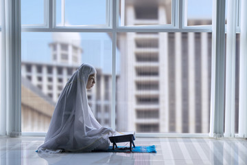 Muslim woman reading the Quran in the mosque