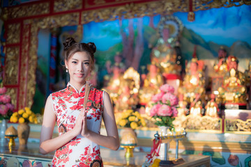 Asian woman wearing chinese dress, smile in chinese new year, Chinese woman dress traditional cheongsam at Chinese Temple.