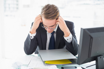 Concentrated businessman reading document at office desk