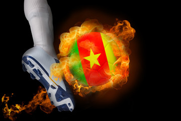Football player kicking flaming cameroon ball against black