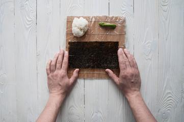 Process of making maki sushi. Cook chef hands preparing rolls with cheese, avocado, salmon and sesame seeds on wooden board