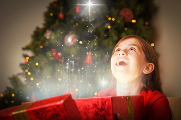 Little girl opening a magical christmas gift against snow