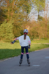 A girl skating with her roller skates in nature on a street with trees next to her