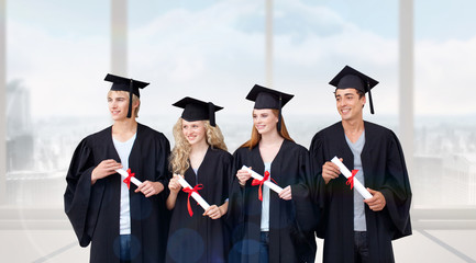Group of people celebrating after Graduation against bright white room with windows