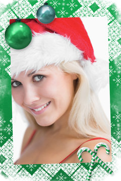 Composite image of a Pretty woman wearing stanta hat against christmas frame