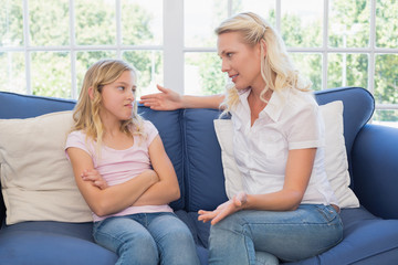 Woman explaining little girl on sofa