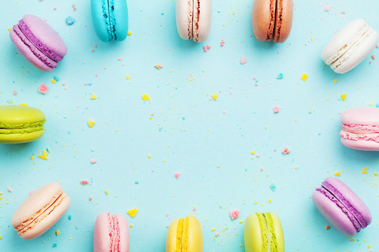 Colorful frame from cake macaron or macaroon on mint pastel background from above. French cookies on dessert top view.