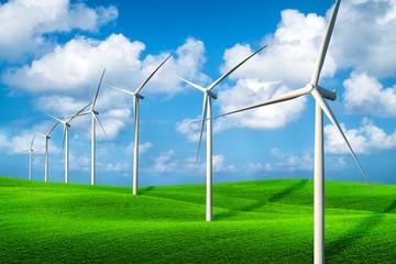 Wind turbines farm on a green grass hills.