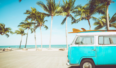 vintage car parked on the tropical beach (seaside) with a surfboard on the roof - Leisure trip in the summer. retro color effect Wall mural