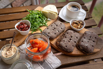 Rye bread sandwich with cream cheese, smoked salmon, arugula, on rustic wooden background, top view. Healthy delicious snack, breakfast or appetizer