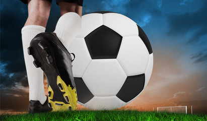 Composite image of football boot kicking huge ball against green grass under blue and orange sky