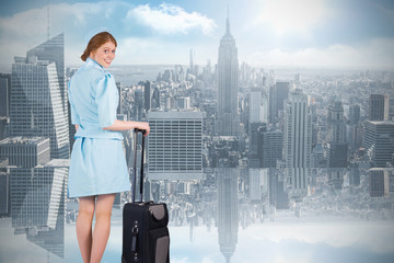 Pretty air hostess leaning on suitcase against room with large window looking on city