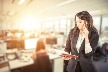 Young attractive businesswoman talking on mobile phone in office,