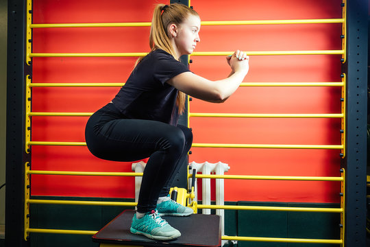 young and beautiful teenage girl doing warm-up and stretching in the gym. woman in black sportswear doing sports