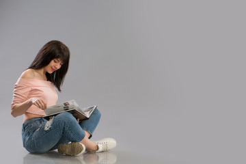 Young woman relaxing on floor reading book on grey background