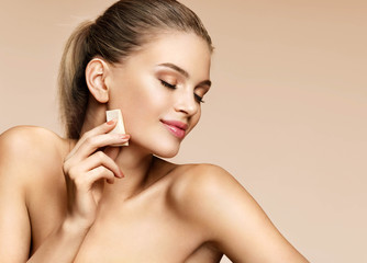 Sensual young girl applying foundation on her face using makeup sponge. Photo of pretty girl of european appearance on beige background. Perfect makeup