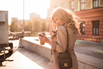 Walking is a spiritual journey and a reflection of living! Warm and sunny professional photo of the young smart model smiling and drinking coffee on the street, while smoothing her wavy hair.