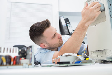 Young it professional repairing cpu on desk