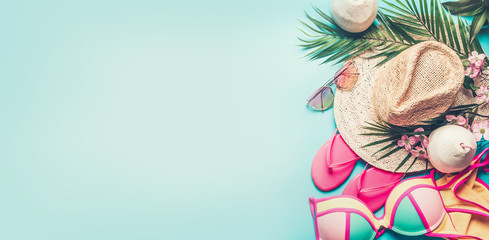 Summer holiday banner. Beach accessories : straw hat, palm leaves, sun glasses, pink  flip flops , bikini and coconut cocktail on blue turquoise background, top view. Tropical vacation travel concept