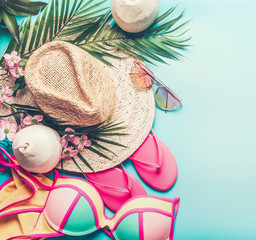 Summer holiday concept. Beach accessories : straw hat, palm leaves, sun glasses, pink  flip flops , bikini and coconut cocktail on blue turquoise background, top view. Tropical vacation travel concept