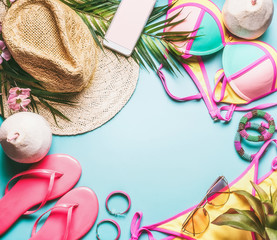 Summer holiday frame. Beach accessories : straw hat, palm leaves, sun glasses, pink  flip flops , bikini and coconut cocktail on blue turquoise background, top view. Tropical vacation travel concept