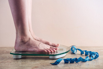 Female feet standing on electronic scales for weight control on light background. Concept of sports training, diets