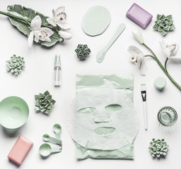 Green skin care cosmetic setting with orchid flowers, accessories and facial calming sheet mask on white background, top view, frame, flat lay. Beauty concept