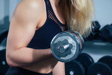 young woman blond doing exercises for the muscles of the hands with a dumbbell in the gym. the girl warmes up and goes in for sports