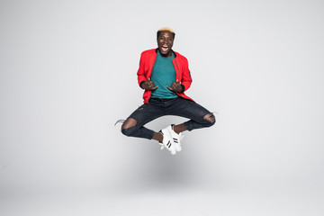Young handsome afro american man jumping over isolated white background.