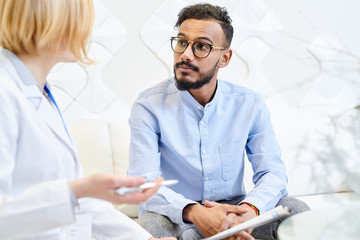 Portrait shot of mixed-race bearded patient sitting on cozy sofa and talking to female physician while having consultation at modern office
