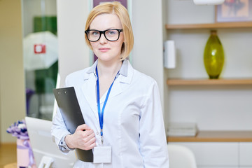 Portrait shot of highly professional doctor wearing white coat and eyeglasses posing for photography while standing at modern office