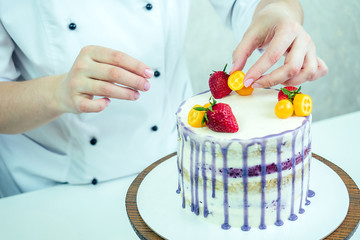 confectioner in black gloves and white work uniform adorns the cake in the kitchen. confectioner, cake, cooking. wedding and birthday cake with berries