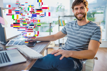 Graphic designer using a graphics tablet against international flags