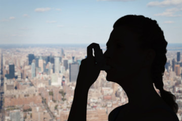 Woman using inhaler for asthma against new york