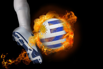 Football player kicking flaming uruguay ball against black