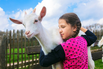 Little girl embracing a kid goat on a farm.