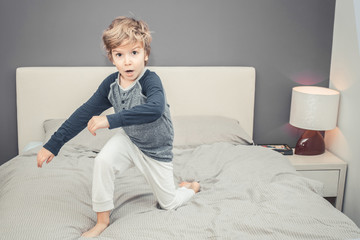 Small boy in pajama playing on the bed.
