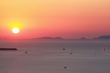 Sunset in orange color on the sea near Santorini island