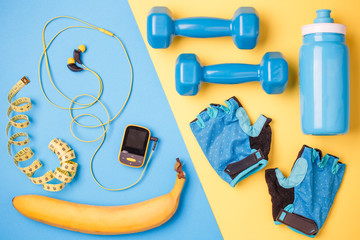 Photo of player, dumbbells, bottle of water, a centimeter tape, gloves, banana on blue and yellow background