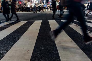 忙しない夜のスクランブル交差点を行きかう人々の足元と横断歩道