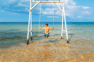 Young man is sitting on a swing against the sea.