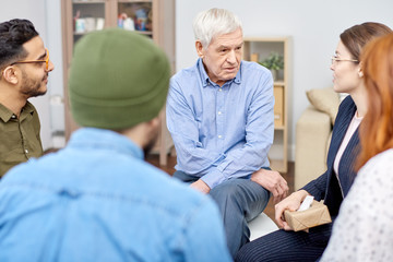 Support group of different age having psychological therapy: they sitting in circle and sharing their problems with highly professional psychologist and other patients