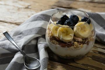 Cup of yogurt muesli, banana and blueberries for breakfast