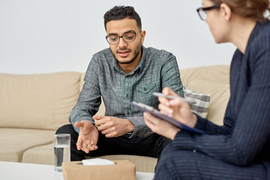 Young mixed-race man wearing eyeglasses sitting on cozy sofa and discussing faced problem with highly professional psychologist during therapy session at cozy office