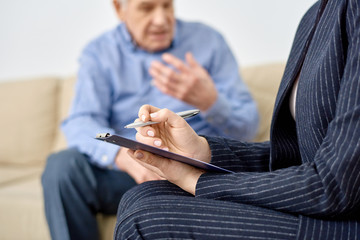 Close-up shot of female psychologist wearing elegant suit taking necessary notes on clipboard while consulting senior patient at modern office