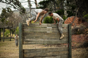 Soldiers climbing wooden wall