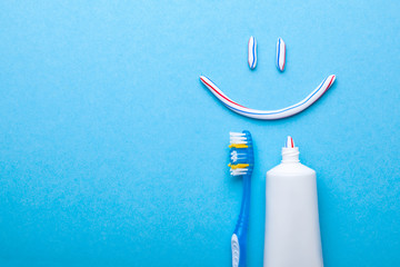 Tooth-paste in the form of face with a smile. Tube of the paste on blue background. Refreshing and whitening toothpaste. Copy space for text