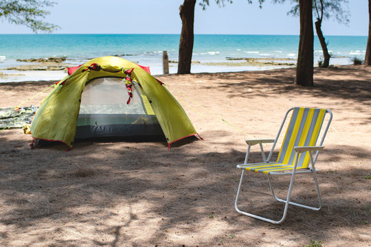 Travellers set their yellow tent and folded chair on the beach by the sea for their relaxation and refresh during holidays