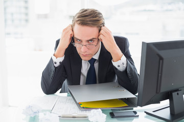 Businessman with documents and computer at office desk