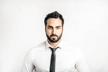 Portrait of bearded eastern man dressed in white shirt and black tie on isolated background